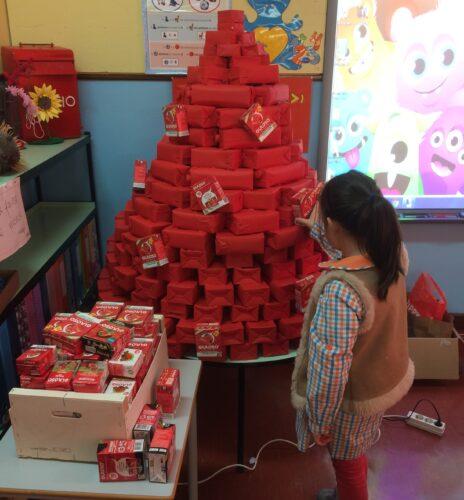 Base pintada de vermelho e colocação dos pacotes Guloso como se fossem bolas de Natal