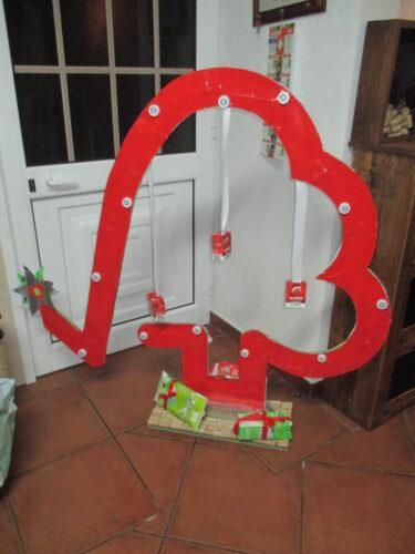 O outro lado da Árvore concluída com o verso dos pacotes Tetra Pak pintados com spray vermelho. Decorado com as tampas e o símbolo Tetra Pak.