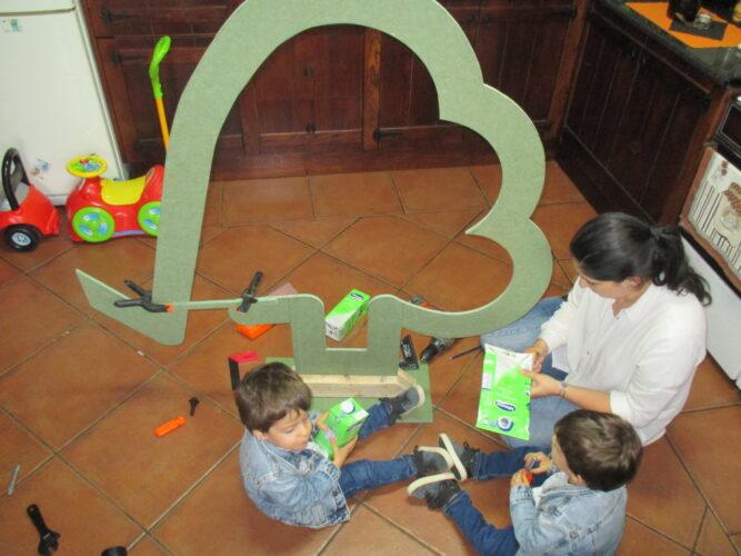 Construção da árvore com a mãe, e as crianças, a abrir os pacotes Tetra Pak.