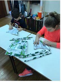 Os alunos formam canudos com os pacotes de leite.