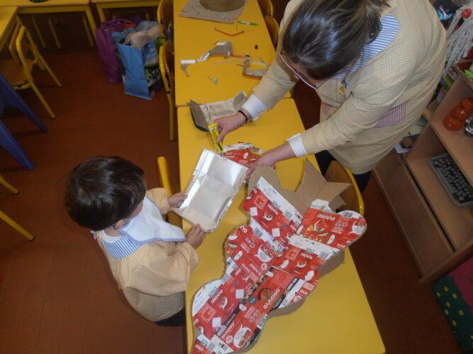 Criança a ajudar a colar os pacotes.