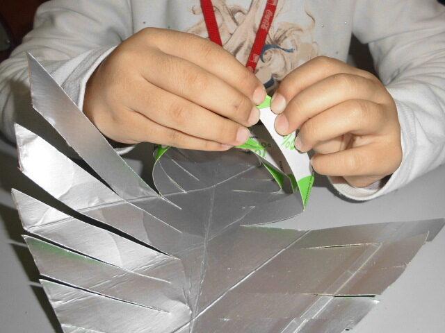 Dobragem da folhas das embalagens de leite para realizar as folhas da árvore
