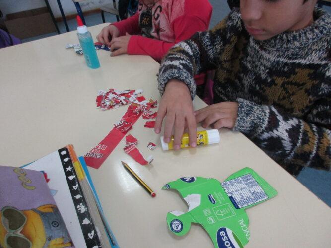 Decoração das embalagens recortadas com formas dos diversos símbolos de Natal, com pedaços de papel de folhetos.