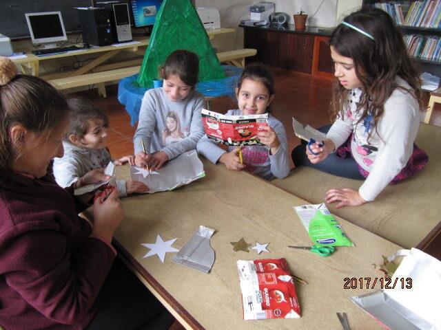Um grupo de alunas está a contornar moldes de estrelas de Natal nas caixas da guloso.