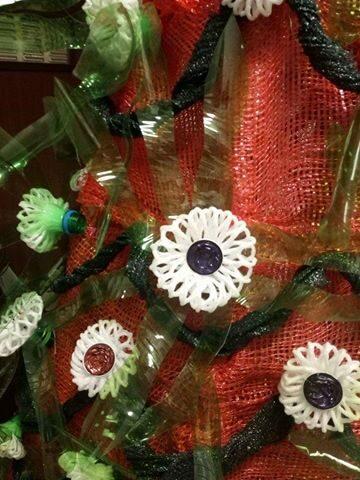 Flores realizadas com garrafas de plástico de sumo, com cápsulas de café e com plástico protetor de garrafas de vidro.